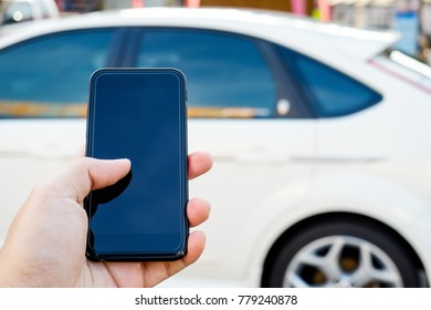 Hand holding smartphone to control car.