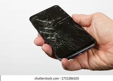 a hand holding a smartphone with cracked display