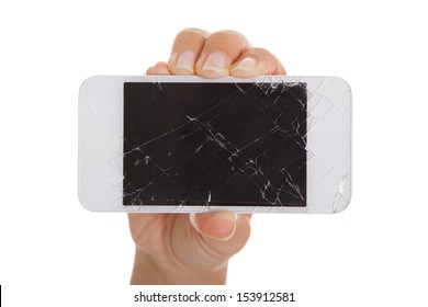 Hand holding smartphone with cracked screen over white background