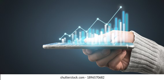 Hand holding smartphone device and touching screen. Stock exchange market concept. Trader looking on with graphs analysis candle