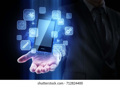 Hand holding smartphone with digital business hologram on dark blue background. Future and infograph concept