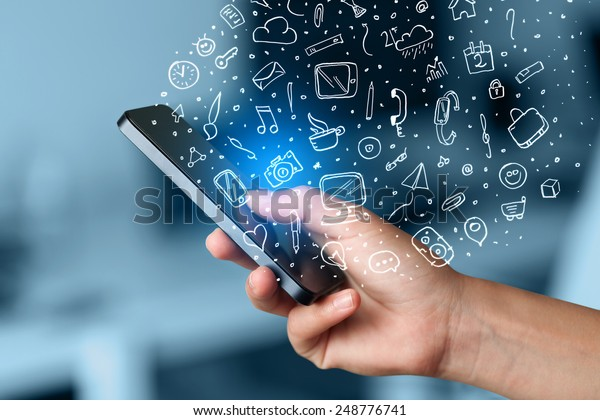 Hand holding smartphone with hand drawn media icons and symbols concept