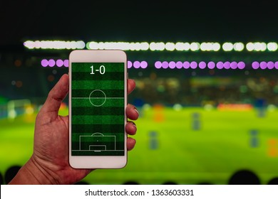 Hand holding smartphone with football field on blur soccer stadium background.