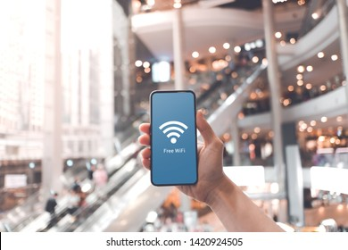 Hand holding smartphone with free wifi icon on blurred shopping mall background.