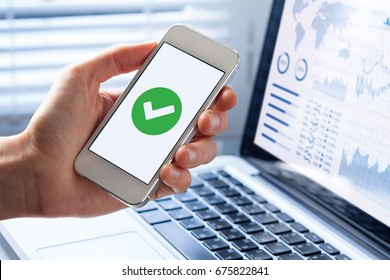 Hand holding a smartphone with a green checkmark icon on the screen to show a validated, confirmed, completed or approved status