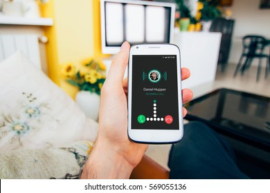 Hand holding smartphone at home with incoming call on the screen.