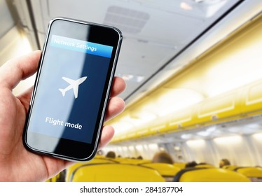Hand holding smartphone inside the plane with flight mode activated