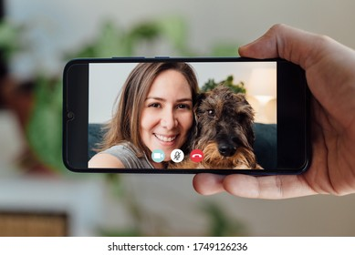 hand holding smartphone making facetime video calling at home, using zoom meeting online app, social distancing, work from home, work remotely concept