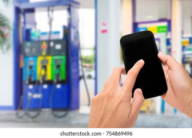 Hand holding smartphone with mobile wallet to pay online at gas station.