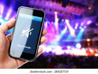 Hand holding smartphone with mute sound on the screen during concert