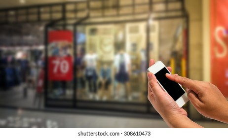 Hand holding smartphone on shopping mall