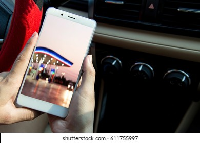 Hand holding smartphone with photo of oil station in car