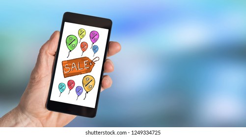 Hand holding a smartphone with sale concept
