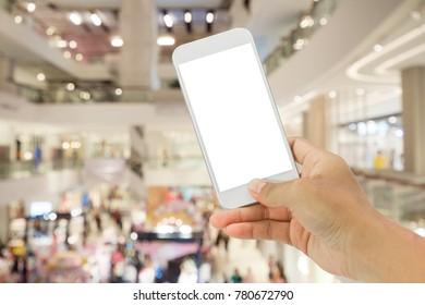 Hand holding smartphone in the shopping mall.