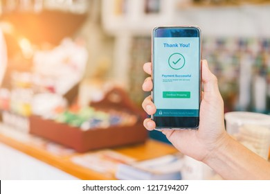 Hand holding smartphone showing payment successful transaction at department store or coffee shop, Cashless technology concept