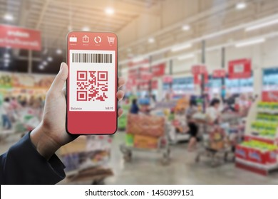 Hand holding a smartphone showing qr code or e-wallet at supermarket. Mobile QR code payment and e-wallet concept.