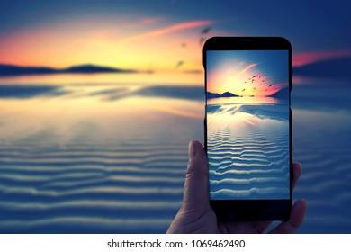Hand holding Smartphone and taking photo of beautiful sunrise at beach