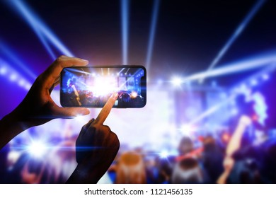 Hand holding smartphone taking photo of live concert party.