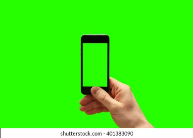 Hand holding smartphone and taking photo on greenscreen background. (Put your own photo behind and inside the phone)