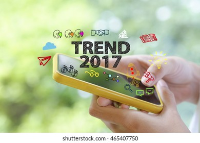 hand holding a smartphone with TREND 2017  concept , business concept