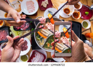 Hand holding a smartphone to use application where to eat buffet with blurred Shabu buffet background ,Freshly sliced pork meat with chopsticks over hot pot and vegetables for shabu and Japanese food.