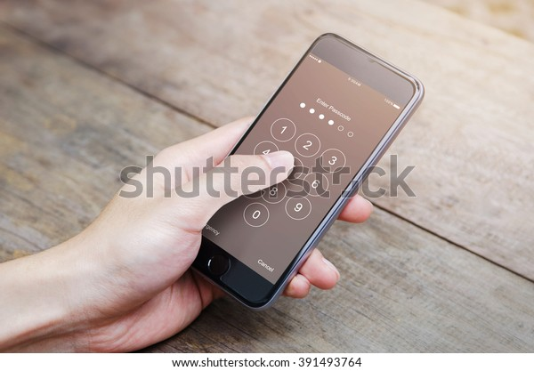 hand holding smartphone while entering the passcode.