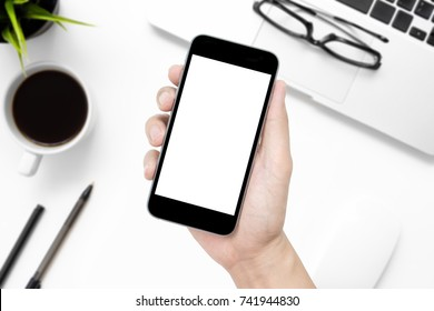 Hand holding smartphone with white blank screen over white office desk table with supplies.