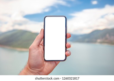 Hand of holding smartphone with white screen on nature background