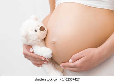Hand holding smiling white teddy bear. Young woman's naked belly. Emotional loving moment in pregnancy time - 30 weeks. Baby expectation. Love, happiness and safety concept. Closeup. Side view.