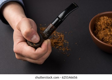 hand holding a smoke pipe with tobacco