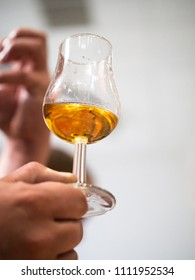 Hand holding a snifter glass filled with whisky, whisky tasting event