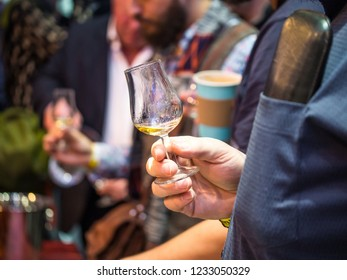 Hand holding a snifter glass at a whisky tasting ceremony