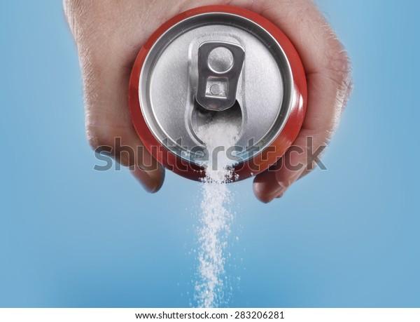 retener a mano puede verter una cantidad loca de azúcar en metáfora del contenido de azúcar de una bebida refrescante aislada en un fondo azul en nutrición saludable, dieta y el concepto de adicción dulce
