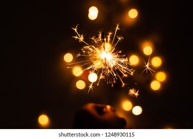 Hand holding sparkler.Abstract and brightly colorful firework in the celebration and anniversary festival.Merry Christmas and New year party light over night sky.