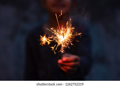 Hand holding sparkler.Abstract and brightly colorful firework in the celebration and anniversary festival.Merry Christmas and New year party light over night sky.Selective focus.