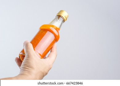 Hand holding spicy red hot sauce in glass bottle for Sukiyaki or hot pot on white background