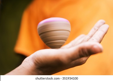 Hand holding spinning top.