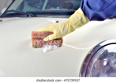 hand holding a sponge for washing the white car with yellow glove inside a parking