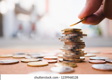 Hand holding stack coins using as business and financial concept