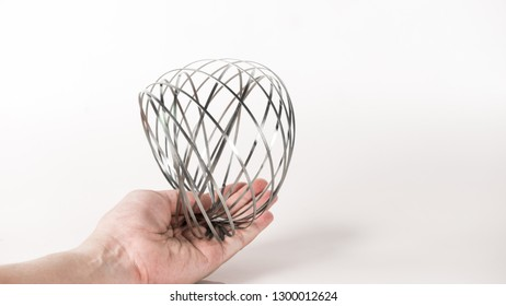 Hand holding stainless steel and elastic spring coil on empty background. Concept of business flexibility. Slightly de-focused and close-up shot. Copy space.