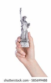 Hand holding a Statue of Liberty souvenir toy on white background. Metal decoration.
