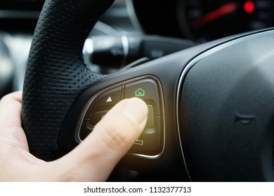 Hand holding steering wheel and thumb pressing Home button switch to automatic drive to home.