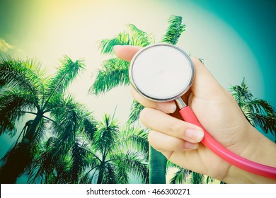 hand holding stethoscope with palm tree and sunlight background