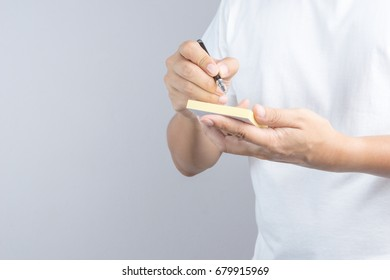 Hand holding sticky note paper sheet on white background