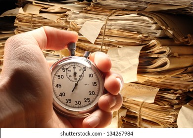Hand holding stopwatch on document folders background