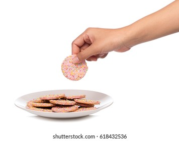 hand holding strawberry cookies with topping sprinkle on dish isolated on white background.