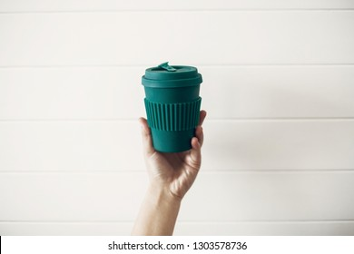Hand holding stylish reusable eco coffee cup on white wooden background. Green Cup from natural  bamboo fiber, zero waste concept. Ban single use plastic. Make a choice. Take away coffee
