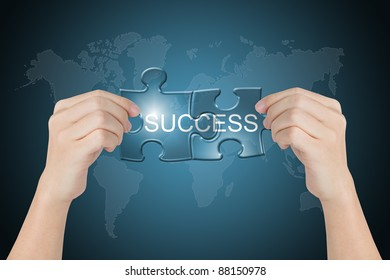 hand holding success connected jigsaw puzzle with world map background