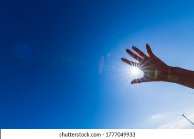 Hand holding up to the sun