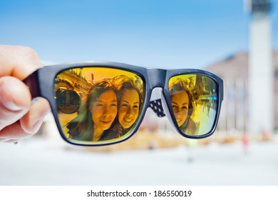 hand holding sunglasses with the reflection of two girls on a blue background Medeo